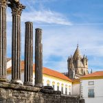 Photo of ancient Roman ruins, highlighted by the columns, inside the town of Evora in Portugal, one of the main tourist sights of the city.