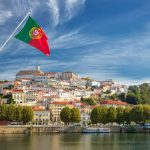 View on the old university city of Coimbra and the medieval capital of Portugal with Portuguese flag, Europe